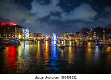 AMSTERDAM, NETHERLANDS - JANUARY 12, 2017: Cruise boats rush in night canals. Light installations on night canals of Amsterdam within Light Festival. January 12, 2017 in Amsterdam - Netherland.