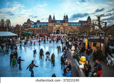 AMSTERDAM, THE NETHERLANDS - JANUARY 15, 2016: Many people skate on winter ice skating rink in front of the Rijksmuseum, a popular touristic destination in Amsterdam, The Netherlands.