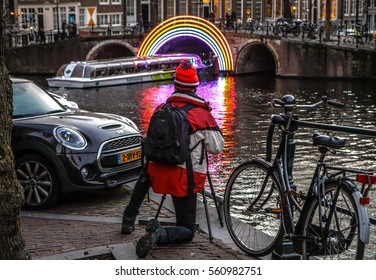 AMSTERDAM, NETHERLANDS - JANUARY 17, 2017: Travel photographer with digital camera making photo of the channel bridge. January 17, 2017 in Amsterdam - Netherlands.