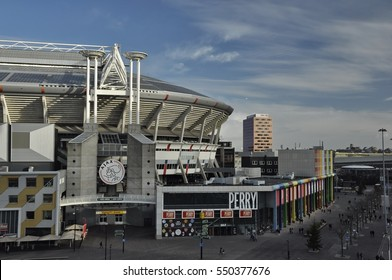 Amsterdam, Netherlands - January 2, 2017: East view of the Amsterdam (Bijlmer) Arena, home of the Ajax soccer team, with the Perry Sport clothing store and pedestrians in the foreground.