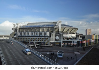 Amsterdam, Netherlands - January 2, 2017: Complete view of the Amsterdam (Bijlmer) Arena, home of the Ajax soccer team, with the Perry Sport clothing store and pedestrians in the foreground.