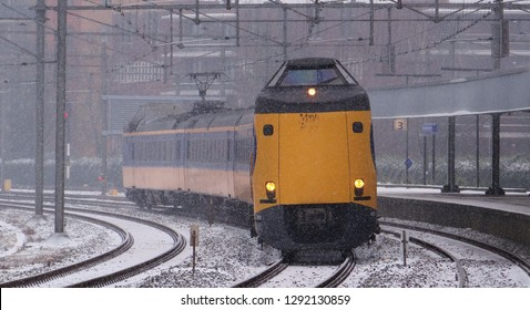 Amsterdam / Netherlands - January 22 2019: A dutch NS intercity train in a track bend near by the railway station of Amsterdam Muiderpoort with heavy snowfall in the winter