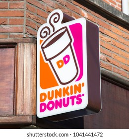AMSTERDAM, THE NETHERLANDS - JANUARY 25th, 2018. Dunkin' Donuts shop sign logo in the city center of Amsterdam. Founded in 1950, Dunkin' Donuts is an American chain.