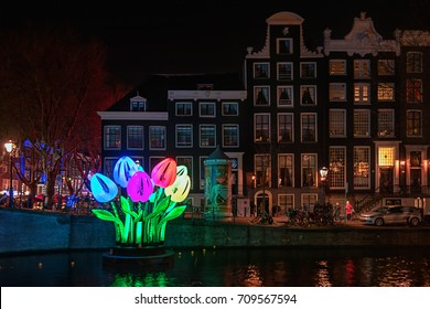 Amsterdam, Netherlands - January 5, 2017: Coloured tulips of light float on a canal during the Festival of Light in Amsterdam