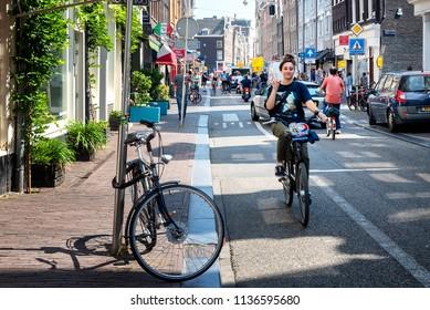 AMSTERDAM, NETHERLANDS - JUL 13: Scene along a busy street in Amsterdam, Holland on July 13, 2018.