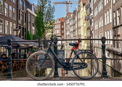 Amsterdam, Netherlands - July 04, 2019:  Amsterdam canals with bicycles on bridges.