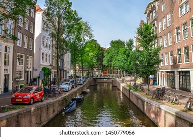 Amsterdam, Netherlands - July 04, 2019:  Amsterdam canals with boats on the embankments. Traditional city view.