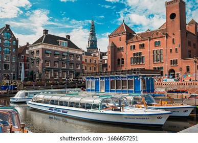 AMSTERDAM, NETHERLANDS - JULY 07, 2015: Cruise boat and historic buildings on background in Old City of Amsterdam - capital of the Netherlands, one of most popular tourist destinations.