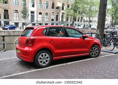 AMSTERDAM, NETHERLANDS - JULY 10, 2017: Red Volkswagen Polo small city car parked by the canal in Amsterdam. Netherlands has 528 registered cars per 1,000 inhabitants.