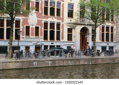 AMSTERDAM, NETHERLANDS - JULY 10, 2017: People visit Herengracht canal in Amsterdam, Netherlands. Amsterdam is the capital city of The Netherlands.
