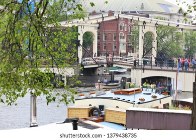 AMSTERDAM, NETHERLANDS - JULY 10, 2017: People visit Magere Brug (The Skinny Bridge) in Amsterdam, Netherlands. Amsterdam is the capital city of The Netherlands.