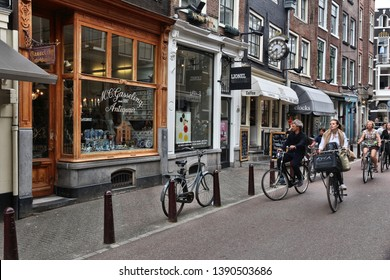 AMSTERDAM, NETHERLANDS - JULY 10, 2017: People cycle along Nieuwe Spiegelstraat, antique shopping street in Amsterdam, Netherlands. Amsterdam is the biggest city and capital of the Netherlands.