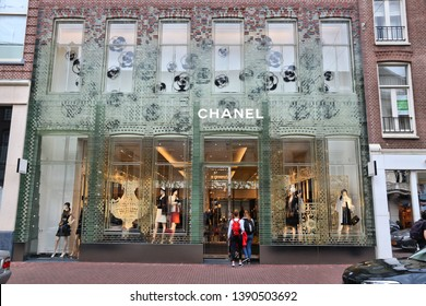 AMSTERDAM, NETHERLANDS - JULY 10, 2017: Person walks by Chanel fashion shop at P.C. Hooftstraat in Amsterdam. Pieter Cornelis Hooftstraat is the ultimate upscale shopping street in the Netherlands.
