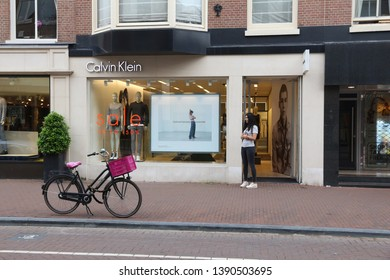 AMSTERDAM, NETHERLANDS - JULY 10, 2017: Person visits Calvin Klein fashion shop at P.C. Hooftstraat in Amsterdam. Pieter Cornelis Hooftstraat is the ultimate upscale shopping street in the Netherlands