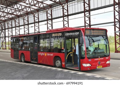 AMSTERDAM, NETHERLANDS - JULY 10, 2017: People ride Connexxion city bus in Amsterdam. Other public transportation bus companies in Amsterdam are GVB and EBS.