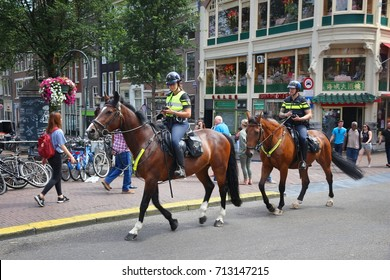 AMSTERDAM, NETHERLANDS - JULY 10, 2017: Equestrian police officers patrol Amsterdam. Police (Politie) employs more than 63,000 people in the Netherlands.