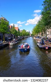 Amsterdam, The Netherlands - July 12, 2017:  Boat filled with passangers cruises down one of the many water canals that meander through the city of Amsterdam.