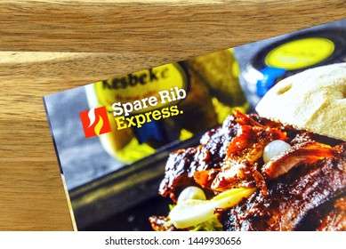 Amsterdam, the Netherlands - July 13, 2019: Part of a sales flyer of Dutch fast food delivery service SpareRib Express, against a wooden background