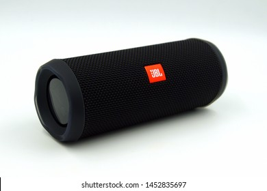 Amsterdam, the Netherlands - July 16, 2019: Black JBL Flip 4 speaker against a white background.