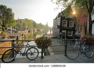 AMSTERDAM, NETHERLANDS - JULY 17, 2019: Sint Antoniesluis lock, overlooking Oudeschans canal, with a crooked heritage building (cafe de Sluyswacht). Picture taken early morning with sun star