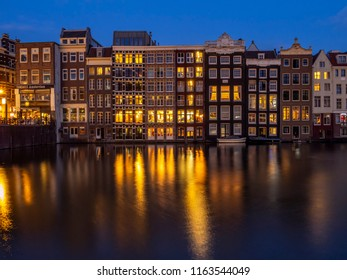 Amsterdam, Netherlands - July 18, 2018: Traditional canal houses on the Damrak at dusk in Amsterdam. Buildings on the canal are a form of traditional Dutch architecture which is now very popular.