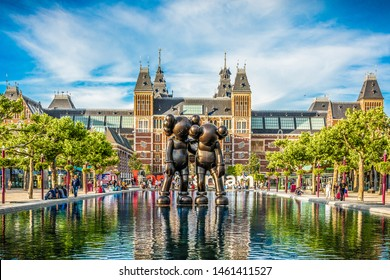 Amsterdam, Netherlands - July 18th 2015: KAWS cartoon mouse character sculpture in front of the Rijksmuseum and famous Amsterdam sign in Amsterdam, the Netherlands (Holland), Europe
