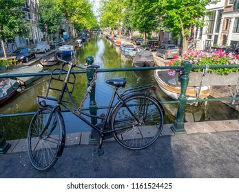 Amsterdam, Netherlands - July 19, 2018: Views along the Egalantiersgracht Canal in the Jordaan District of Amsterdam. There are many bridges with flowers and bikes in Amsterdam.