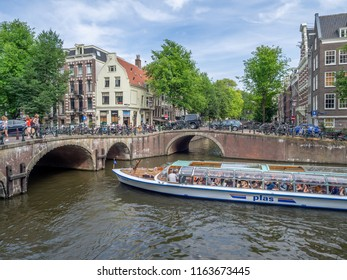 Amsterdam, Netherlands - July 20, 2018: Buildings and tour boat on the Prinsengracht Canal in the Jordaan district    in the heart of the Netherlands beautiful capital city of Amsterdam.