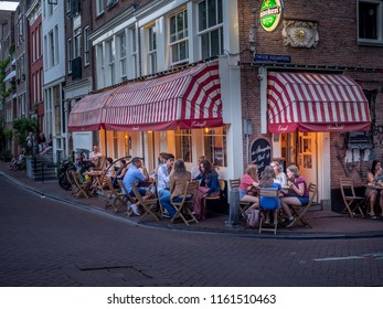 Amsterdam, Netherlands - July 21, 2018:  A busy outdoor restaurant in the Jordaan district of Amsterdam in the evening. Outdoor restaurants are popular during the warm summer nights.
