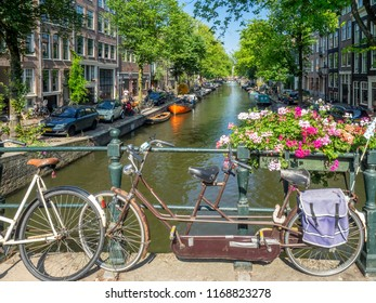 Amsterdam, Netherlands - July 22, 2018: Old bicycles along a bridge over a canal in Amsterdam. There are bikes locked up on many canals as it is a popular mode of transportation here.