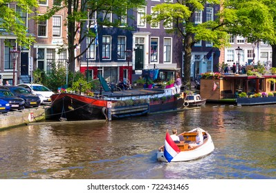 Amsterdam, Netherlands - July 23 2016: People travel by boat along the canals of Amsterdam at summer time.