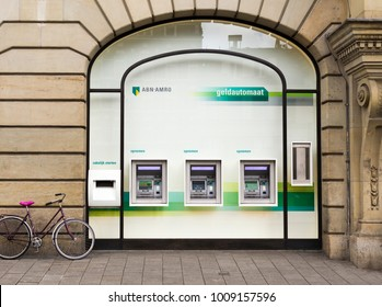 AMSTERDAM, NETHERLANDS - JULY 24, 2017: Automated teller machines in display window of ABN AMRO Bank N.V. and parked near it bicycle on the Leidseplein Square in Amsterdam. Three street ATMs and bike.