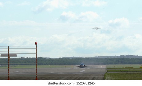 AMSTERDAM, NETHERLANDS - JULY 25, 2017: Fokker F70 of KLM airlines taking off. Turboprop twin engine airplane approaching behind