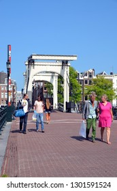 AMSTERDAM, NETHERLANDS - JULY 26, 2014: Tourists walk across the Skinny bridge (Magere brug) over the Amstel river  in Amsterdam, Holland