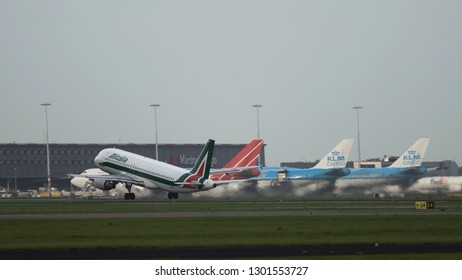 AMSTERDAM, NETHERLANDS - JULY 26, 2017: Side view of Airbus A320 EI-IKF of Alitalia airlines accelrates on runway and take off