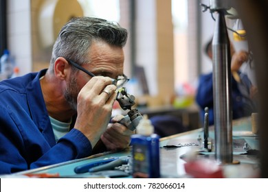 Amsterdam, Netherlands - July 27 2017: A skilled worker inspects a diamond they are shaping at the Gassan Diamond factory in Amsterdam, Netherlands.