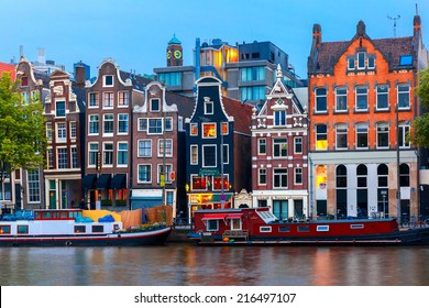 Amsterdam, Netherlands - July 30, 2014: Night city view of Amsterdam canal, typical dutch houses and boats, Holland. Canal ring area placed on the UNESCO World Heritage List.