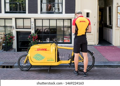 AMSTERDAM, THE NETHERLANDS - JULY 4, 2019: DHL courier with freight bicycle. DHL is a division of the German logistics company Deutsche Post AG providing international express mail services.