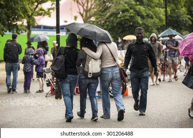 Amsterdam, The Netherlands - July, 5 2015: visitors walking under the rain during Amsterdam Roots Open Air, a cultural festival held in Park Frankendael on 05/07/2015