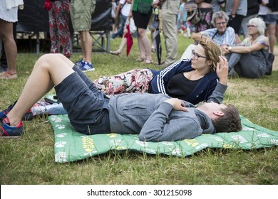Amsterdam, The Netherlands - July, 5 2015: young couple lying in the grass during Amsterdam Roots Open Air, a cultural festival held in Park Frankendael on 05/07/2015