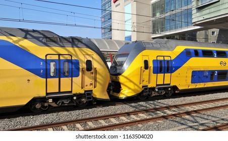 Amsterdam / Netherlands - July 6 2018: Two Dutch NS yellow and blue double decker trains (VIRM) with the logo of the NS at the central station of Amsterdam.