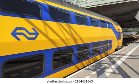 Amsterdam / Netherlands - July 6 2018: A Dutch NS yellow and blue double decker train with the logo of the NS at the central station of Amsterdam.