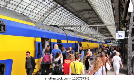 Amsterdam / Netherlands - July 6 2018: A Dutch modern NS train with many passengers boarding at the busy platform at Amsterdam Central Station. (crowd)