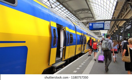 Amsterdam / Netherlands - July 6 2018: A Dutch modern NS InterCity train with passengers boarding at the busy platform at Amsterdam Central Station.