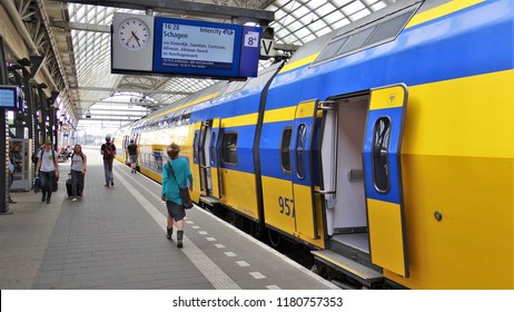 Amsterdam / Netherlands - July 6 2018: A Dutch modern NS InterCity train with passengers boarding at the busy platform at Amsterdam Central Station. (with travel information board)