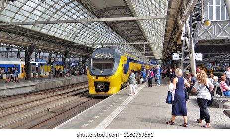 Amsterdam / Netherlands - July 6 2018: A Dutch modern NS train with many passengers at the platform at Amsterdam Central Station. (crowd)
