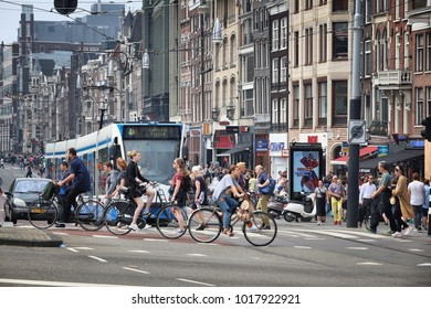 AMSTERDAM, NETHERLANDS - JULY 7, 2017: People visit Damrak shopping street in Amsterdam, Netherlands. Amsterdam is the biggest city and capital of the Netherlands.