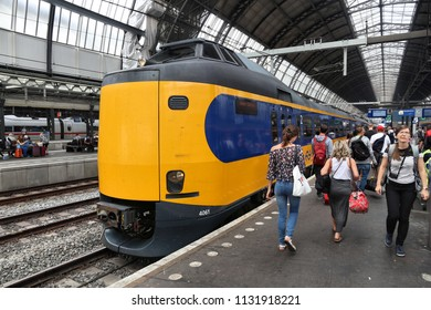 AMSTERDAM, NETHERLANDS - JULY 7, 2017: People exit Nederlandse Spoorwegen (NS) train in Amsterdam. NS is the principal Dutch public railway company, operating 4,800 domestic trains daily.