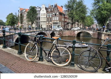 AMSTERDAM, NETHERLANDS - JULY 7, 2017: People visit Leidsegracht and Keizersgracht canal crossing in Amsterdam, Netherlands. Amsterdam is the capital city of The Netherlands.