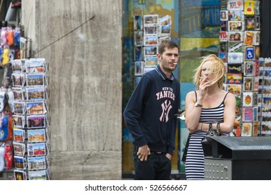 AMSTERDAM, NETHERLANDS - JULY 8, 2015: A couple smokes standing in the street in front of a shop selling postcards.